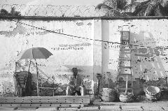 Starting a new day. A bricklayer sitting on the street with his equipment, waiting for daily job.